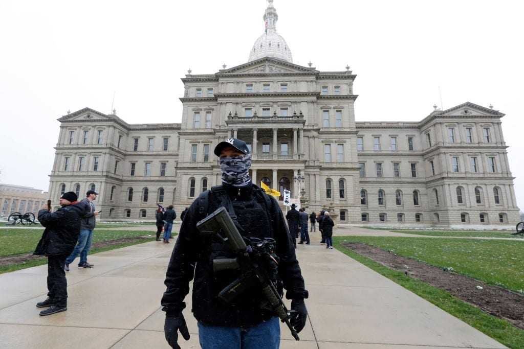 """People take part in a protest for """"Michiganders Against Excessive Quarantine"""" at the Michigan State Capitol in Lansing, Michigan"""